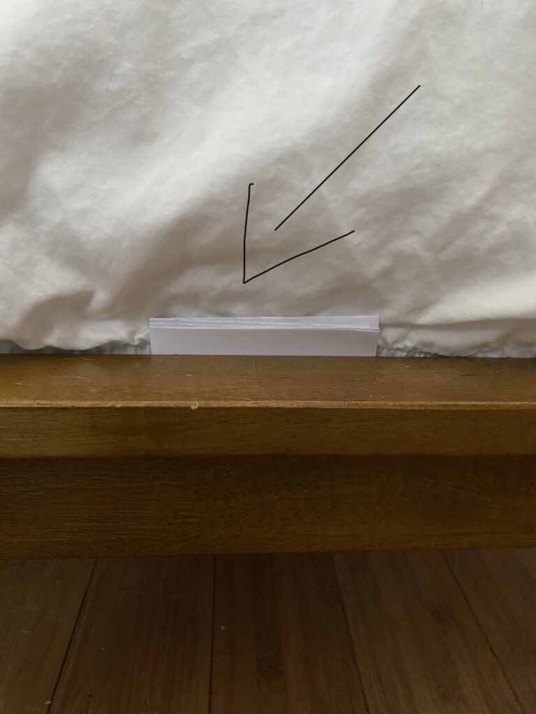 DIY paper monitor for bed bugs - placed on the side of a mattress.